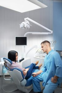 Male dentist talking to a patient in a clinic